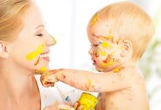 Il bambino sporco felice estrae le pitture sul suo fronte della madre Fotografie Stock Libere da Diritti