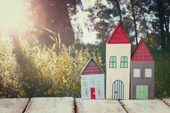 Immagine della decorazione variopinta di legno d'annata delle case sulla tavola di legno davanti alla foresta della campagna Immagini Stock