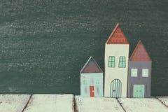 Immagine della decorazione variopinta di legno d'annata delle case sulla tavola di legno davanti alla lavagna retro immagine filt Immagine Stock Libera da Diritti