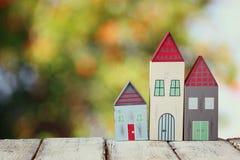 Immagine della decorazione variopinta di legno d'annata delle case sulla tavola di legno davanti a fondo blured Fotografia Stock