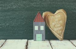 Immagine delle case variopinte di legno d'annata e del cuore del tessuto sulla tavola di legno davanti alla lavagna retro immagin Fotografia Stock