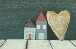 Immagine delle case variopinte di legno d'annata e del cuore del tessuto sulla tavola di legno davanti alla lavagna retro immagin Immagini Stock Libere da Diritti