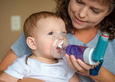 Infant getting breathing treatment from mother Stock Photography