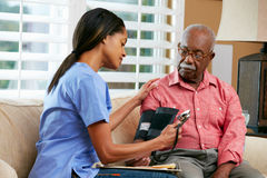 Infirmière rendant visite au patient mâle supérieur à la maison Photo stock