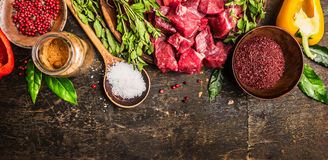 Ingredients for goulash or stew cooking: raw meat, herbs,spices,vegetables and spoon of salt on rustic wooden background, top view Royalty Free Stock Photography