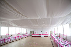 The inside of a massive white wedding tent with ta Royalty Free Stock Photo