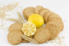 Integrale Kekse und verzierte Zitrone auf weißem Hintergrund Lizenzfreie Stockfotografie
