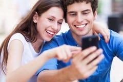 Jong paar die mobiele telefoon bekijken Royalty-vrije Stock Fotografie