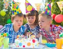 Jonge geitjes bij de blazende kaarsen van de verjaardagspartij op cake Stock Afbeeldingen