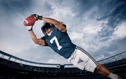 Jugador de fútbol americano que coge un paso de momento del aterrizaje Foto de archivo libre de regalías