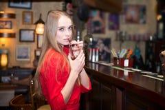Junge schöne Frau trinkende coctails an der Stange Stockfotos