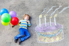Kid boy having fun with colorful birthday cake drawing with chal Royalty Free Stock Photos