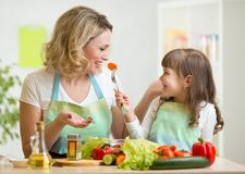 Kid girl and mother eating healthy food vegetables Stock Photos