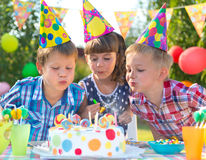 Kids at birthday party blowing candles on cake Stock Images