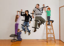 Kids teamwork taping parents to wall Royalty Free Stock Photos