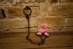 Kids teddy bear prisoner in jail chains Stock Photo