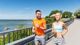 Lächelnde Paare, die an der Sommerküste laufen Lizenzfreie Stockfotos