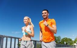 Lächelnde Paare, die an der Sommerküste laufen Lizenzfreies Stockfoto