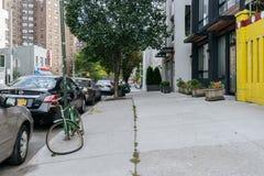 La bici dimenticata e tagliata è attaccata ad un palo al bordo della t Fotografia Stock Libera da Diritti