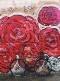 la bicyclette Gris-noire de fixie devant le mur avec le rouge lumineux fleurit le graffiti Image libre de droits