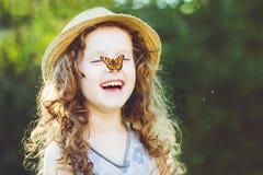 Lachendes gelocktes Mädchen mit einem Schmetterling auf seiner Hand Glückliches childhoo Stockbild