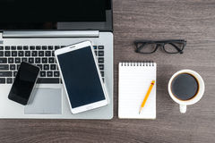 Laptop Mobile Phone and Tablet with notebook on the desk Stock Photos