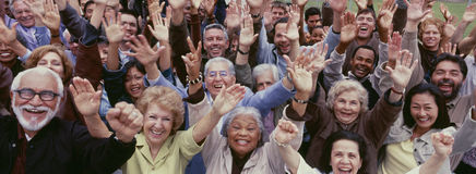 Large group of multi-ethnic people cheering with arms raised Stock Image