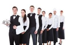 Large group of waiters and waitresses standing in row Royalty Free Stock Images