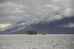 Lastkahn geschleppt durch Schlepper in Küsten-Alaska-Wolken und im Gebirgshintergrund Stockfotografie