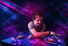 Le jeune DJ jouant sur des plaques tournantes avec des effets de la lumière de couleur Image stock