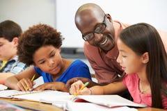 Lehrer Helping Pupils Studying an den Schreibtischen im Klassenzimmer Lizenzfreie Stockbilder