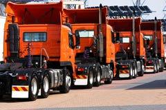 Line of heavy haulage orange trucks Royalty Free Stock Images