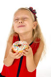 Little beautiful female child with long blonde hair and red dress eating sugar donut with toppings delighted and happy Royalty Free Stock Images
