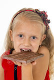 Little beautiful female child in red dress holding happy delicious chocolate bar in her hands eating delighted Stock Images