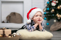 Little boy in Christmas decorations expect a miracle Stock Photo