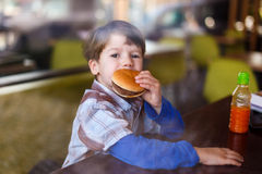 Little boy in fast food restaurant eat hamburger Royalty Free Stock Photography