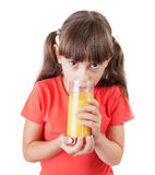 Little girl with an appetite drinking juice Stock Image