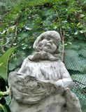 Little girl and holding fruit basket sculpture and green vine in English Garden Stock Image