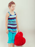 Little girl kid with red heart shape pillow. Royalty Free Stock Image