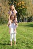 Little girl sitting on girls´ shoulders Royalty Free Stock Photo