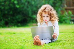 Little girl sitting on grass and playing tablet pc, toning photo Royalty Free Stock Images