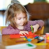 Little preschooler girl cutting paper Royalty Free Stock Photo