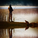 Lone fisherman catches fish Stock Images