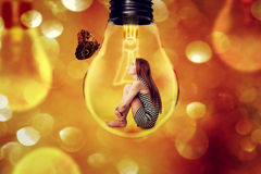 Lonely woman sitting inside light bulb looking at butterfly Royalty Free Stock Image