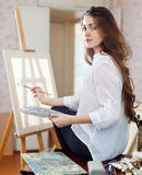 Long-haired woman with oil colors near easel Royalty Free Stock Photo