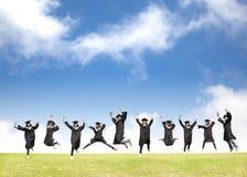 Los estudiantes celebran la graduación y el salto feliz Fotografía de archivo libre de regalías