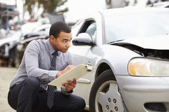 Loss Adjuster Inspecting Car Involved In Accident Royalty Free Stock Photos