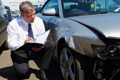 Loss Adjuster Inspecting Car Involved In Accident Stock Image