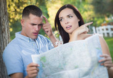 Lost and Confused Mixed Race Couple Looking Over Map Outside Stock Images