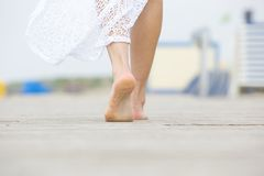 Low angle barefoot woman walking away Stock Images